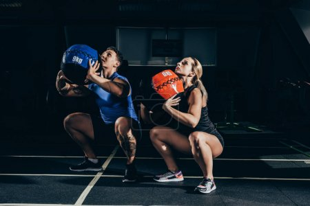 Photo for Young athletic man and woman squatting with weighted balls at gym - Royalty Free Image