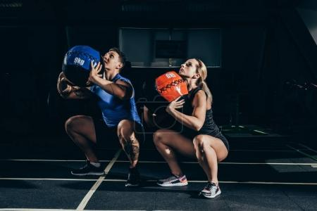 Couple squatting with weighted balls