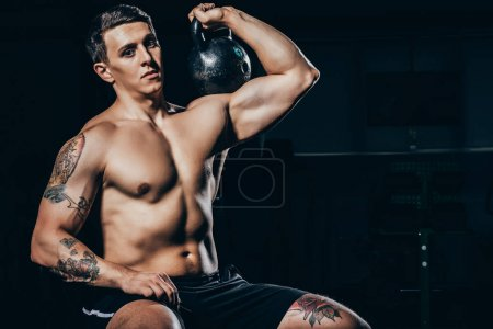 Photo for Shirtless young sportsman with embossed muscles holding a kettlebell on his shoulder - Royalty Free Image