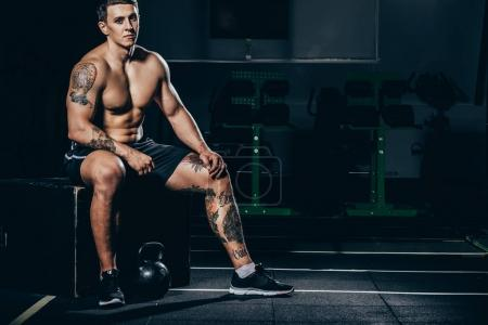 Photo for Shirtless young sportsman with embossed muscles sitting at gym with kettlebell placed on floor - Royalty Free Image