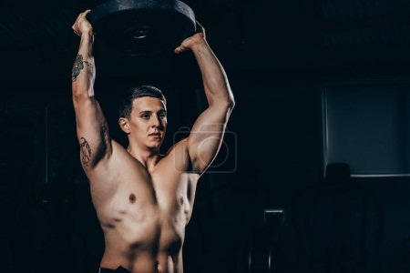 Photo for Shirtless young sportsman with embossed muscles holding a barbell weight - Royalty Free Image