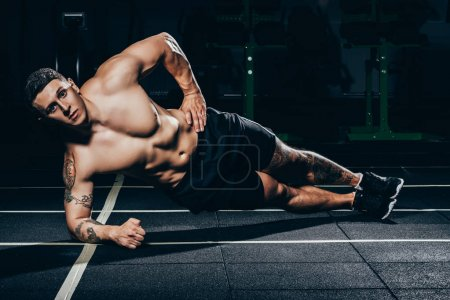 Photo for Shirtless young sportsman with embossed muscles doing a side plank - Royalty Free Image