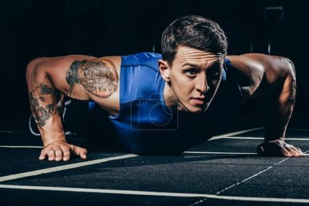 Photo for Young athletic sportsman with tattoos and embossed muscles doing push ups - Royalty Free Image