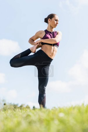 Photo for Young athletic woman stretching leg outdoors on grass - Royalty Free Image
