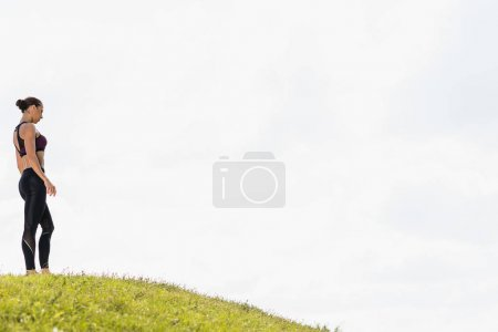 fit woman standing on grass hill