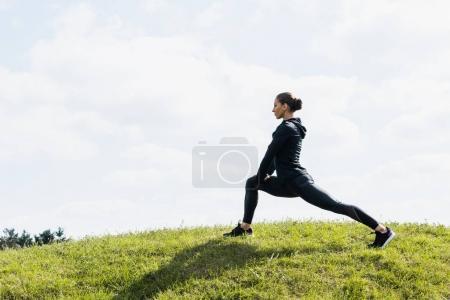 Photo pour Jeune femme en forme étirant les jambes sur le champ d'herbe - image libre de droit