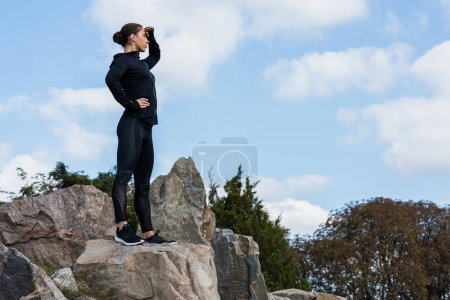 woman standing on rocks and looking away
