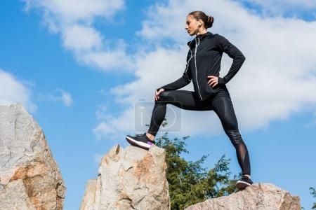 Photo for Bottom view of beautiful sportive woman standing on rocks - Royalty Free Image