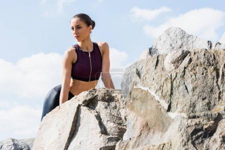 sportswoman posing on rocks