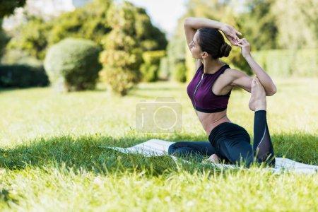 Photo pour Belle femme en Pigeon poser pratiquant d'yoga à l'extérieur sur l'herbe - image libre de droit