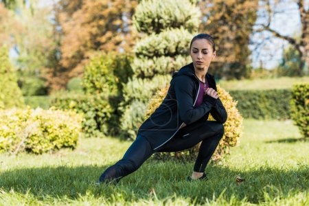 Photo for Concentrated young woman stretching legs in autumn park - Royalty Free Image