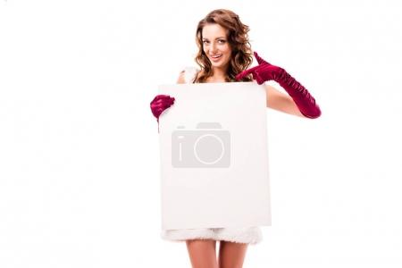 Photo for Attractive girl in santa costume pointing at empty board, isolated on white - Royalty Free Image