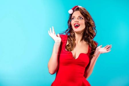 Photo for Excited attractive girl in santa hat, isolated on blue - Royalty Free Image