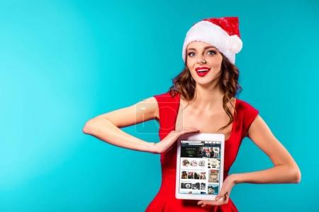 Photo for Beautiful girl in santa costume presenting digital tablet with amazon website on christmas, isolated on blue - Royalty Free Image