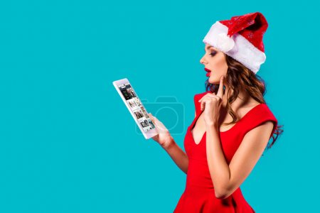 Photo for Beautiful girl in santa costume using digital tablet with amazon website, isolated on blue - Royalty Free Image