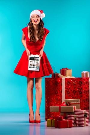 Photo for Beautiful girl in santa costume standing at gifts and presenting digital tablet with amazon website, on turquoise - Royalty Free Image