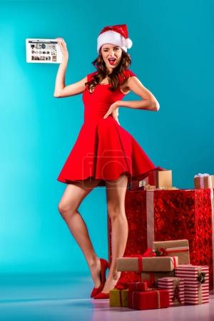 Photo for Attractive girl in santa costume winking, standing at gifts and presenting digital tablet with amazon website, on turquoise - Royalty Free Image