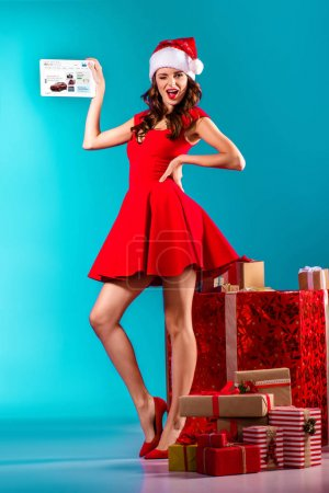 Photo for Attractive girl in santa costume winking, standing at gifts and presenting digital tablet with ebay website, on turquoise - Royalty Free Image