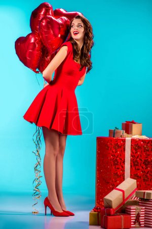 cheerful girl with balloons and presents