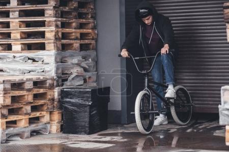 Photo pour Voir toute la longueur du jeune homme au casque de vélo bmx à l'extérieur - image libre de droit
