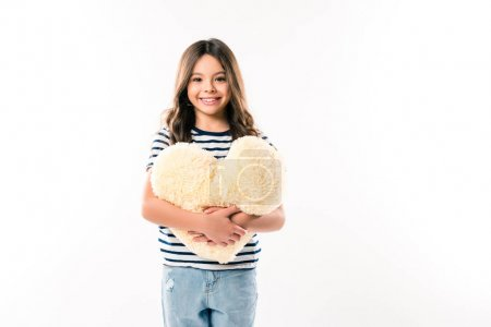 kid holding heart shaped pillow