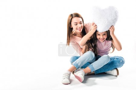 Mother and daughter playing with pillow