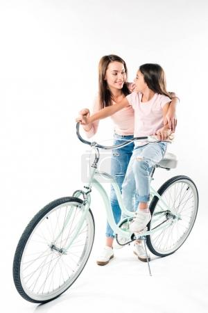 Mother teaching daughter riding bicycle