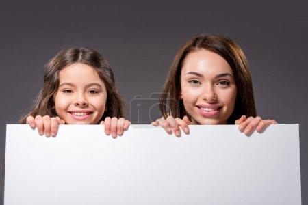 Photo pour Mère et fille tenant tableau blanc vide isolé sur gris - image libre de droit