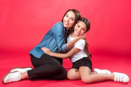 Photo for Daughter and mother sitting and hugging on red - Royalty Free Image