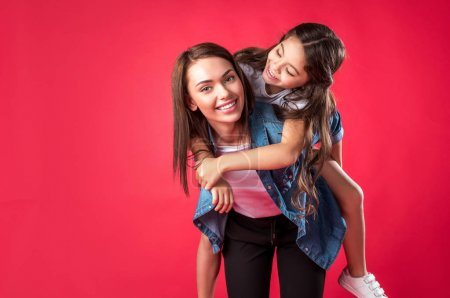 Mother giving piggyback to daughter