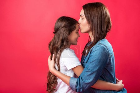 Mother kissing daughter in forehead