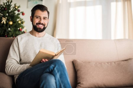 Photo pour Bel homme lisant un livre à la maison et regardant la caméra - image libre de droit