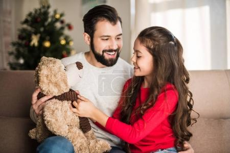 father showing happy daughter teddy bear