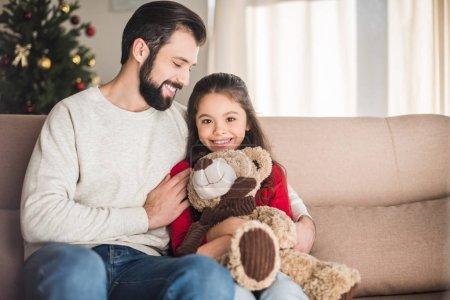 Photo pour Souriant père fille étreignant avec ours en peluche - image libre de droit