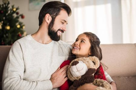 father hugging daughter with teddy bear