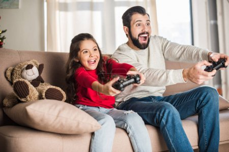 Photo for Excited father and daughter playing video game at home - Royalty Free Image