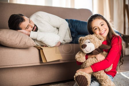 father sleeping on sofa and daughter sitting with teddy bear
