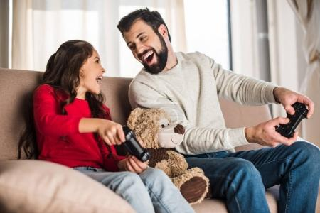 Photo for Happy father and daughter playing video game at home and looking at each other - Royalty Free Image