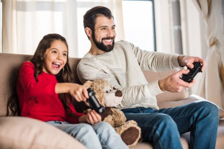 Photo for Smiling father and daughter playing video game at home - Royalty Free Image