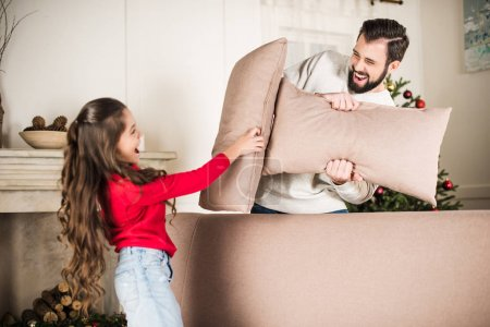 father and daughter beating with sofa pillows at home