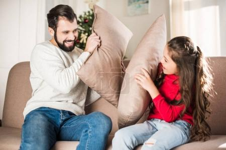 happy father and daughter beating with pillows at home