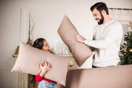 father and daughter beating with pillows at home