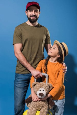 father and daughter standing with luggage and teddy bear on blue