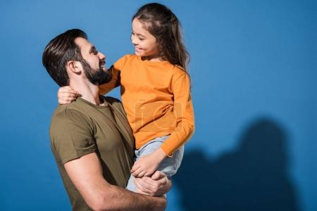 handsome father holding smiling daughter on blue