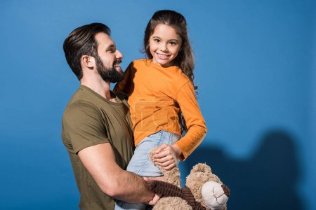 handsome father holding daughter on blue