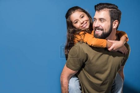 Photo for Father giving piggyback to smiling daughter on blue - Royalty Free Image