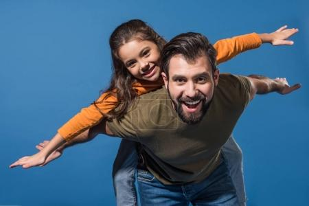 Photo for Father giving piggyback to daughter on blue - Royalty Free Image