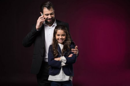 father talking by smartphone and hugging smiling daughter with crossed hands on burgundy