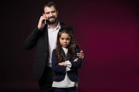 father talking by smartphone and hugging serious daughter with crossed hands on burgundy