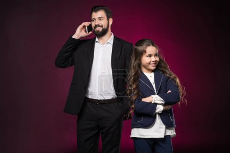 father talking by smartphone and daughter standing with crossed hands on burgundy